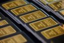 Gold retreats from three-week high on stronger dollar